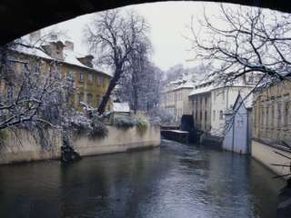 Snow Covered Trees and Houses Backing onto Canal Certovka, Prague
